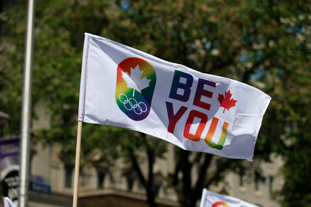 """Flag displacing a rainbow Canadian Olympic Committee logo and the words """"Be You"""""""
