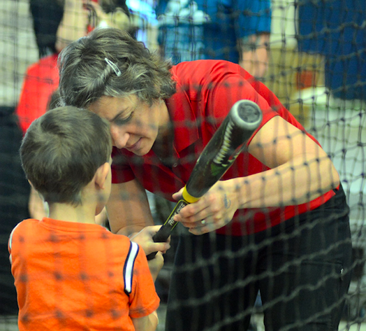 Athlete teaches a child where to place their hands on a baseball bat